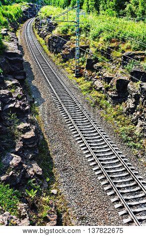 railroad tracks run between the mountains transportation