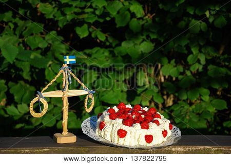 Strawberry cake and a midsummer decoration in a garden