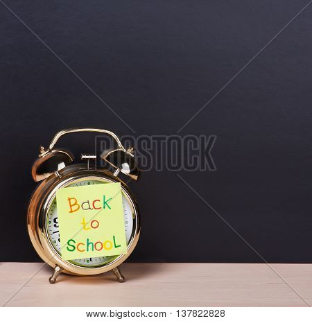 alarm clock and sticker with text back to school on the school board background