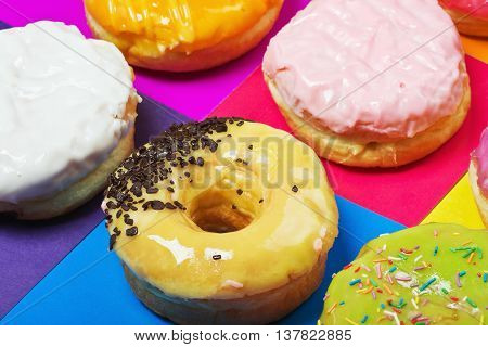 colored glazed donuts on a colored background