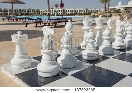 Closeup of playing pieces on giant chess boards game in tropical hotel resort with swimming pool