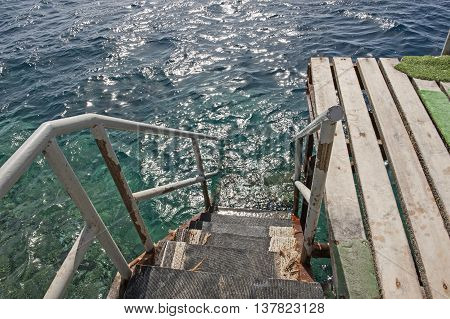 Steps on wooden jetty going down into water of tropical ocean