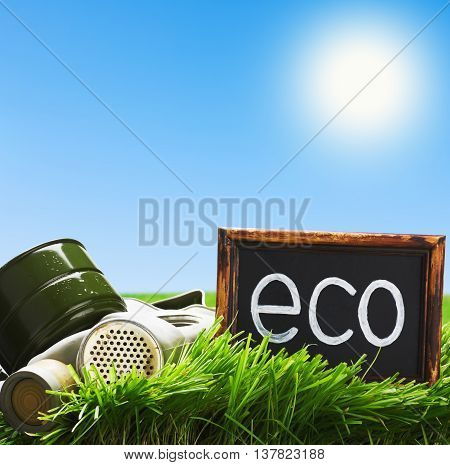 gas mask and a black board with the word ecology against the blue sky