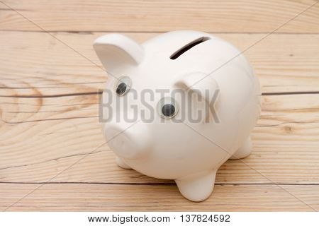 Added to your Saving A white piggy bank on weathered wood