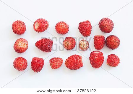 Macro view wild strawberry on white background. Forest berries in rectangular shape form. Shallow depth of field.