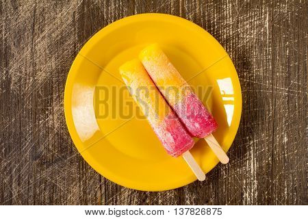 Two Raspberry and Orange ice pops on a yellow plate