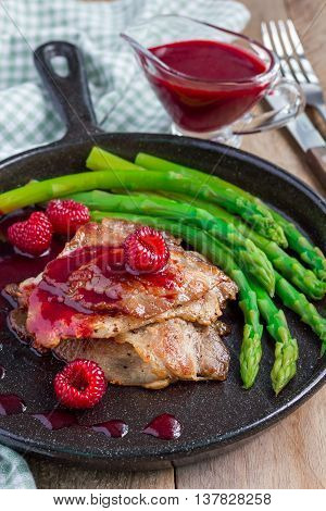 Pork cutlets with raspberry sauce and asparagus in iron cast pan vertical