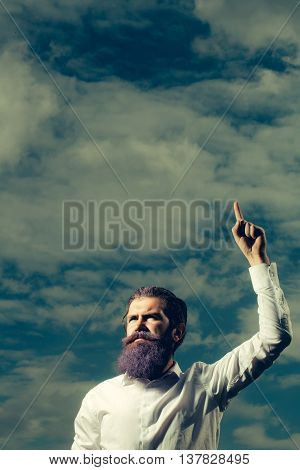 young handsome bearded man with long beard blue color and serious face in white shirt sunny day outdoor on natural cloudy sky background