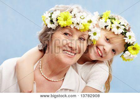 Portrait of granddaughter embracing her grandmother on a blue background