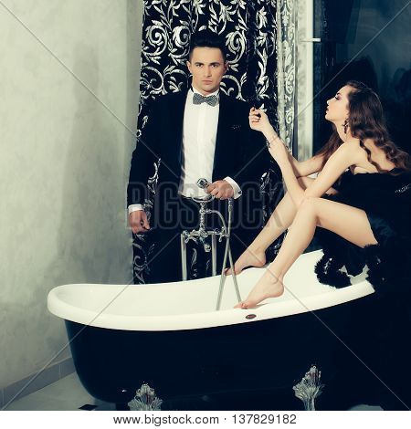 young handsome man in black suit and bow with pretty sexy woman in elegant evening dress with skirt and long curly hair sitting in bath