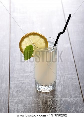 Home made lemonade in a glass with a leaf of mint, a slice of lemon and a straw on a wooden table, lateral view