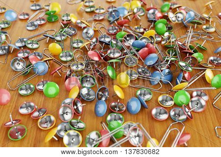 Office colored paper clips and drawing pins scattered on a table. Illustration 3d