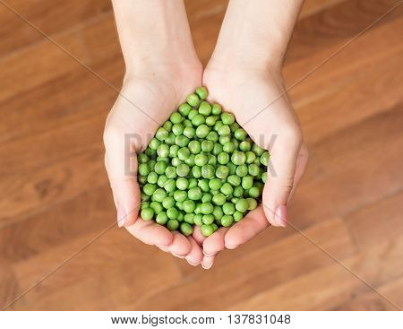 Woman's hands holding green peas. Heart shape from peas
