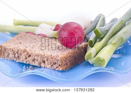 Slice of rye bread and green goods on a blue saucer