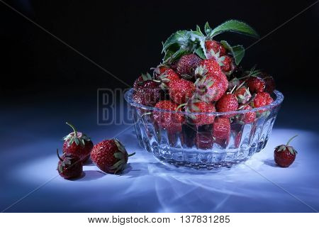Berries of strawberry and merry in a glass vase. Light brush
