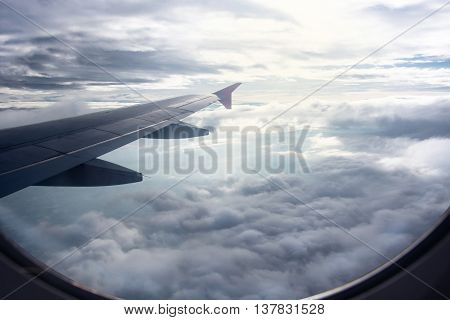 View of beautiful raincloud and wing of airplane from window view of through window aircraft during flight in wing with raining sky