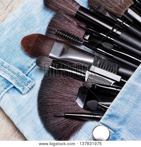 Professional tools of make-up artist in blue jeans pocket. Sponge tip applicators and makeup brushes: for applying foundation, powder, blush, eyeshadow, eyebrow brushes and others. Selective focus