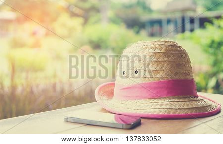 Farmer Hat with smart phone for Modern hi technology farmer on table vintage tone.