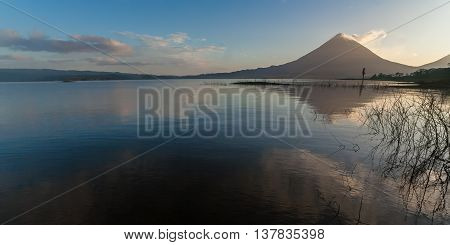 Volcano Arenal in Costa Rica at dawn with reflection in the water