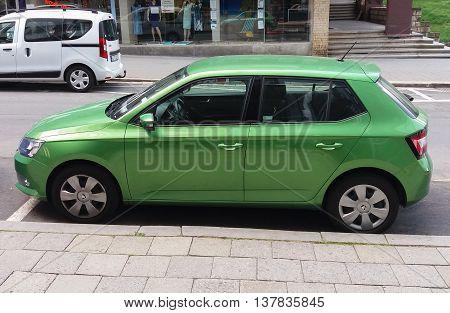 PRAGUE CZECH REPUBLIC - CIRCA JUNE 2016: light green Skoda Fabia car parked on a street of the city centre