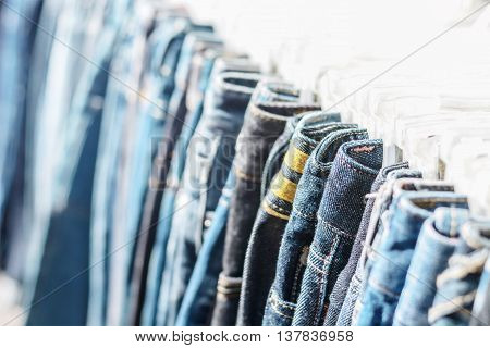 Row of hanged blue jeans in a shop selective focus on jeans