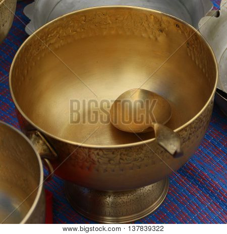 hammered copper pedestal bowl with copper spoon on red and blue mat, Songkhla, Thailand