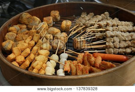 grilled Thai meatball skewers over coals in round grill pan, Songkhla, Thailand