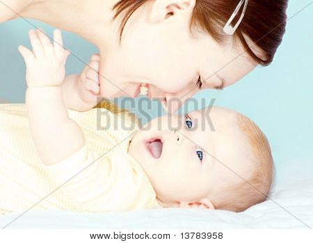 Young mother is playing with her little baby girl
