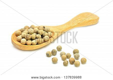White peppers and wooden spoon on white background