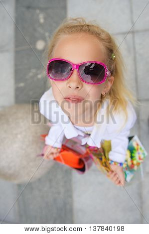 Fashionably dressed little girl with shopping bags. Young little girl with full shopping bags standing near boutique. Blond girl in sunglasses. Point of shooting from above. Girl looking at camera.
