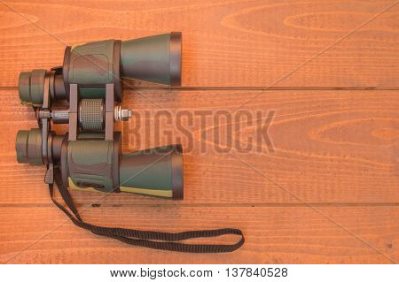Binoculars protective khaki on wooden background, top view.