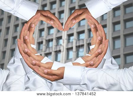 Hand of men concatenation a heart shape and have Skyscraper of background.