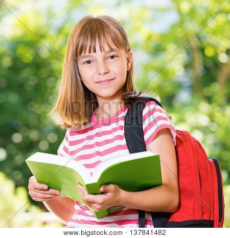 Outdoor portrait of happy girl 10-11 year old with backpack reading book. Back to school concept.