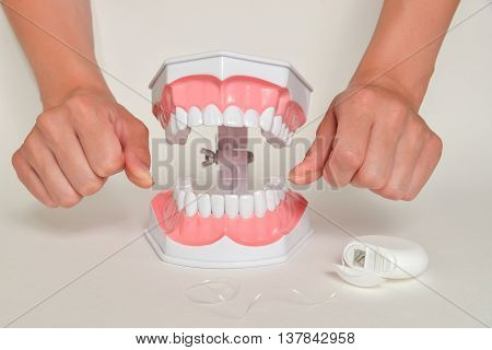 Showing how to use floss, dental care concept.