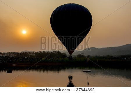 silhouette of hot air balloon on lake in sunset time