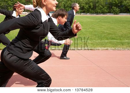 Image of active employees running down sport track