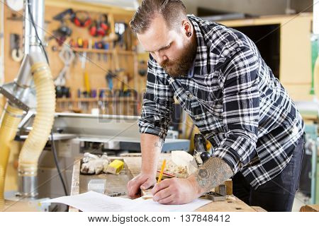 Adult craftsman looks at drawing in a work shop for wood work and construction. Carpenter designs and prepares new work.