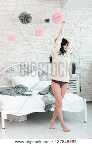 Hardly awaking woman in white pullover. Young brunette in white pullover and panties early in morning in her bedroom with raised hands barefoot on tiptoe