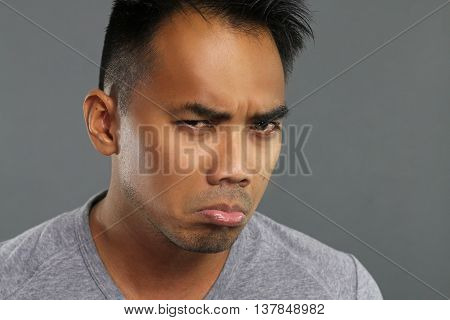 Grumpy young man over a gray background