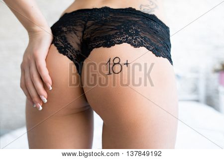 Seductively touching ass women with remark 18plus. Sexy buttocks in black panties with text 18plus on it. Unrecognizable sexy woman caressing her ass closeup