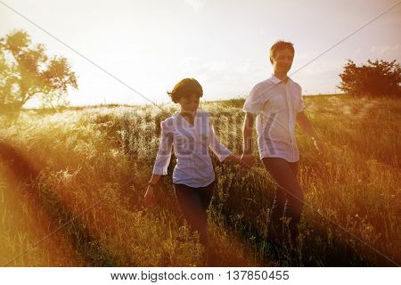 Happy couple holding hands walking through a meadow, tinted photo.