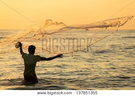 Kochi, India - January 3, 2016: Silhouette of the unidentified Indian fisherman throwing net in sea on sunset in Fort Kochi, India.