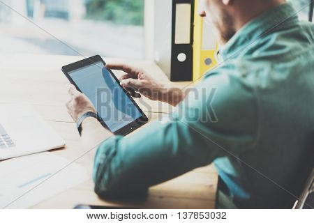 Social Trading Online Markets Analyze Reports.Man Working wood table Modern Interior Design Loft Place.Businessman Work Coworking Studio.Using Digital Tablet Hands.Blurred Background.Business Startup