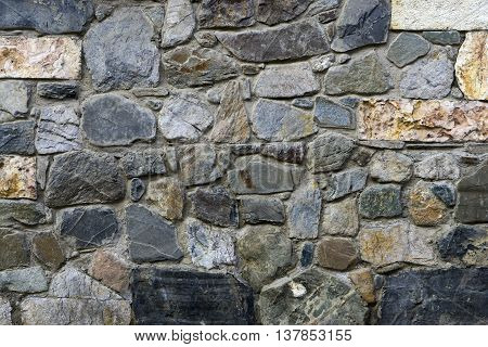 texture, the background of the wall lined with natural stones of different shapes sizes and colors