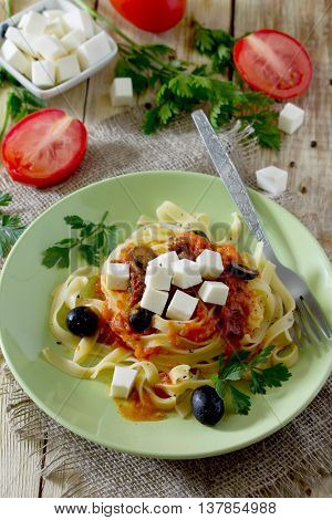Italian Pasta Tagliatelle With Tomato Sauce With Sun-dried Tomatoes, Feta Cheese Garnished With Pars