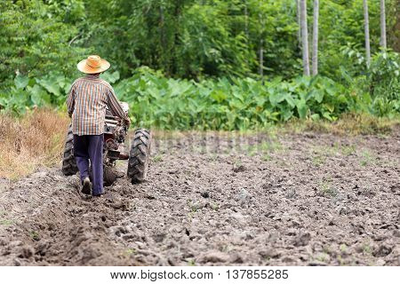 Farmers is working control pushcart to recondition soil crop for Rice Cultivation area.