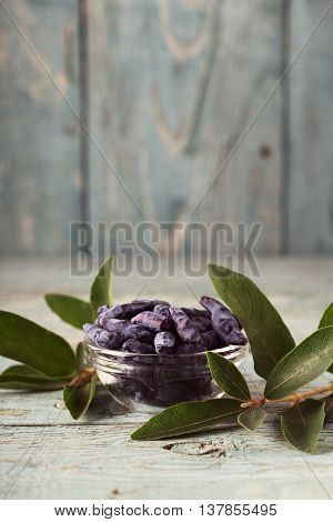 Bowl of honeysuckle berry on wooden background. Space for text