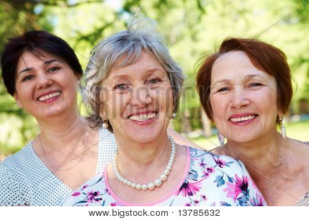 Portrait of three aged women looking at camera with smiles