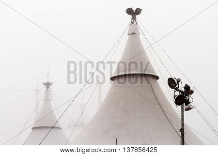 Cones circus tent with headlights in the fog