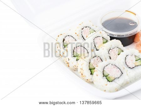 Set of sushi rolls served in a delivery container package, composition isolated over the white background, close-up crop foreshortening